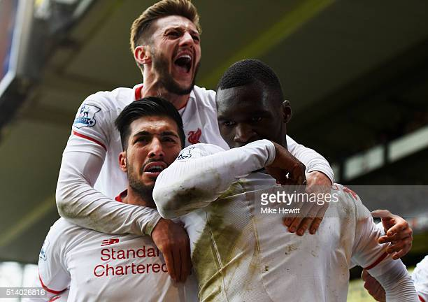 Christian Benteke of Liverpool celebrates with team mates Emre Can and Adam Lallana as he scores their second goal from the penalty spot during the...