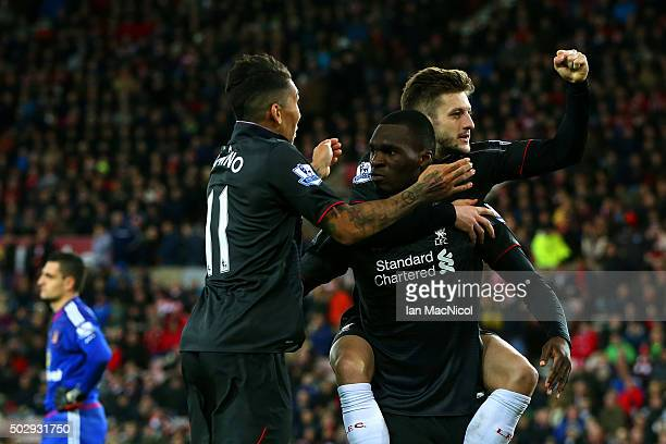 Christian Benteke of Liverpool celebrates with teammate Adam Lallana and Roberto Firmino of Liverpool as Vito Mannone of Sunderland shows his...