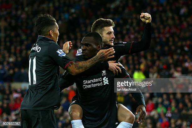 Christian Benteke of Liverpool celebrates with teammates Adam Lallana and Roberto Firmino of Liverpool during the Barclays Premier League match...