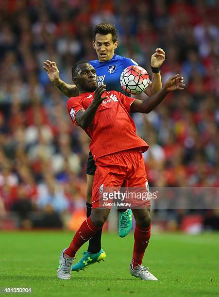 Christian Benteke of Liverpool is challenged by Charlie Daniels of Bournemouth during the Barclays Premier League match between Liverpool and AFC...