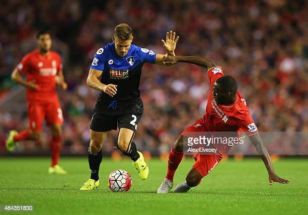 Christian Benteke of Liverpool is challenged by Simon Francis of Bournemouth during the Barclays Premier League match between Liverpool and AFC...