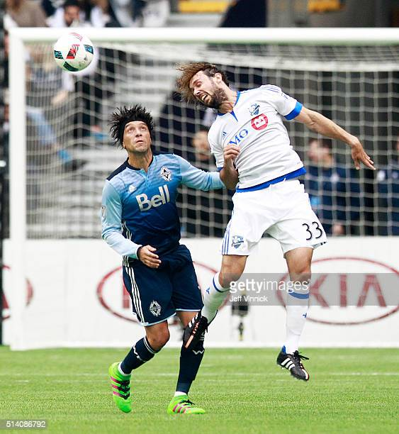 Christian Bolanos of the Vancouver Whitecaps looks on as Marco Donadel of the Montreal Impact heads the ball during their MLS game March 6 2016 at BC...
