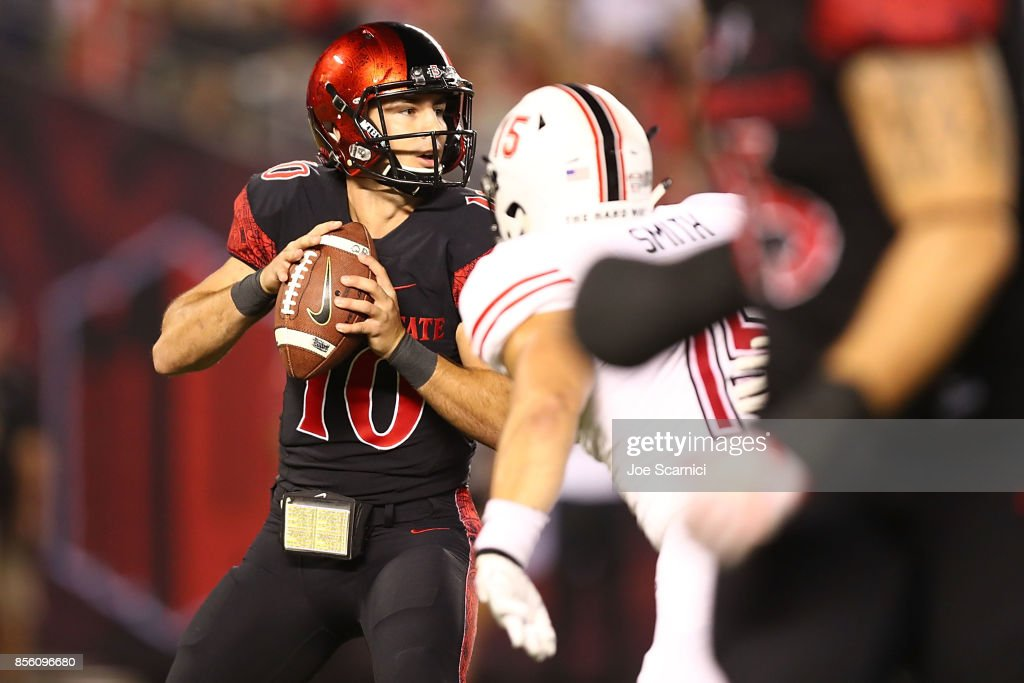 Christian Chapman #10 of the San Diego Aztecs is tackled by Sutton Smith #15 of the Northern Illinois Huskies in the first quarter during the Northern Illinois v San Diego State game at Qualcomm Stadium on September 30, 2017 in San Diego, California.
