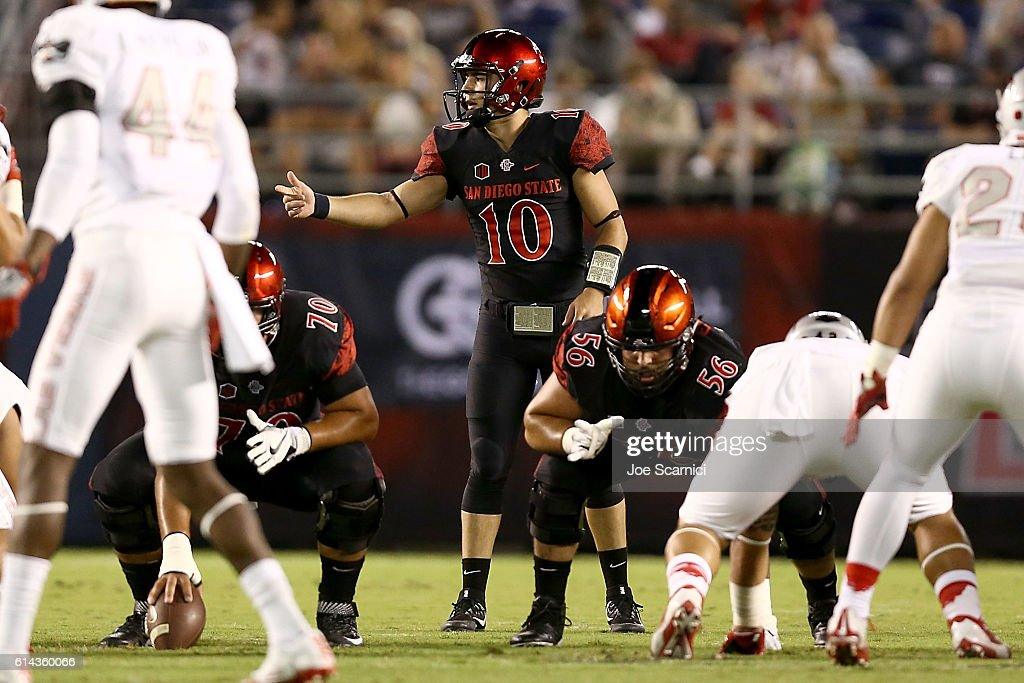 Christian Chapman #10 of the San Diego State Aztecs makes a call from the line of scrimmage as Arthur Flores #70 and Nico Siragusa #56 prepare to play in the first quarter of the UNLV v San Diego State game at Qualcomm Stadium on October 8, 2016 in San Diego, California.