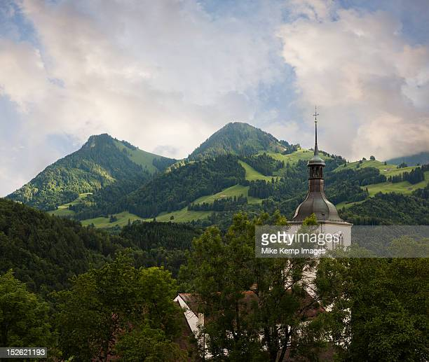 Christian church spire surrounded by  Swiss Alps