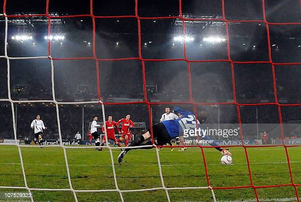 Christian Clemens of 1 FC Koeln scores against Ralf Faehrmann of Eintracht Frankfurt the first goal during the Bundesliga match between 1FC Koeln and...