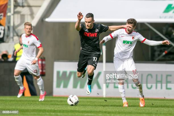 Christian Clemens of Cologne and Daniel Baier of FC Augsburg in action during the Bundesliga match between FC Augsburg and 1 FC Koeln at WWK Arena on...