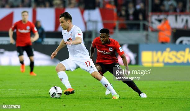 Christian Clemens of Cologne in action against Taleb Tawatha of Frankfurt during the German Bundesliga soccer match between 1 FC Cologne and...