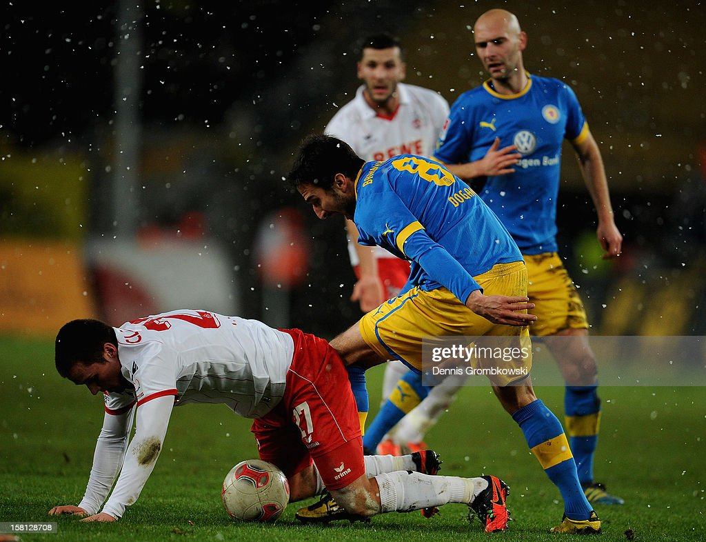 Christian Clemens of Cologne is challenged by Deniz Dogan of Braunschweig during the Bundesliga match between 1. FC Koeln and Eintracht Braunschweig at RheinEnergieStadion on December 10, 2012 in Cologne, Germany.