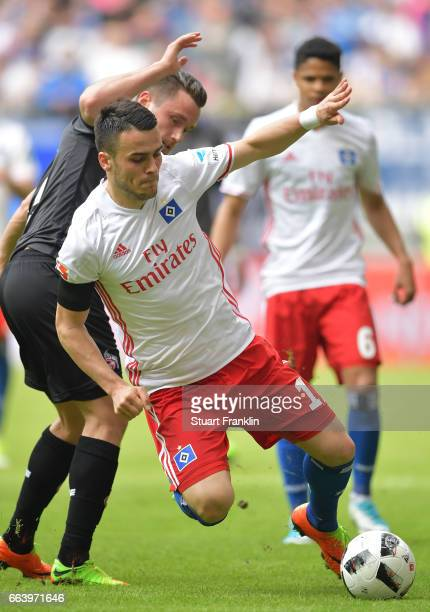 Christian Clemens of Cologne is challenged by Filip Kostic of Hamburg during the Bundesliga match between Hamburger SV and 1 FC Koeln at...