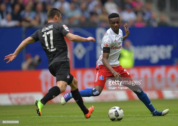 Christian Clemens of Cologne is challenged by Gideon Jung of Hamburg during the Bundesliga match between Hamburger SV and 1 FC Koeln at...