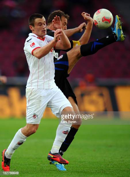 Christian Clemens of Koeln challenges Bjoern Schlicke of Frankfurt during the Second Bundesliga match betweeen 1 FC Koeln and FSV Frankfurt at...