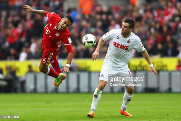 Christian Clemens of Koeln fouls Thiago of Bayern Munich during the Bundesliga match between 1 FC Koeln and Bayern Muenchen at RheinEnergieStadion on...