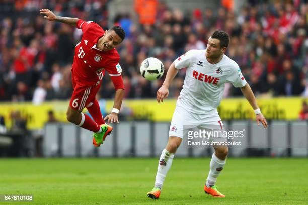 Christian Clemens of Koeln fouls Thiago of Bayern Munich during the Bundesliga match between 1 FC Koeln and Bayern Muenchen at RheinEnergieStadion on...
