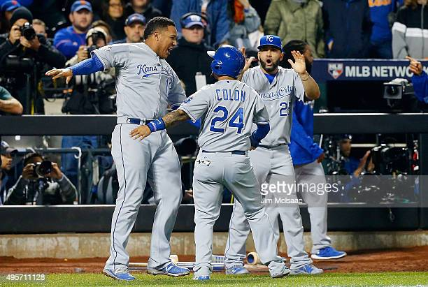 Christian Colon of the Kansas City Royals celebrates after scoring a run in the 12th inning against the New York Mets with teammates Salvador Perez...