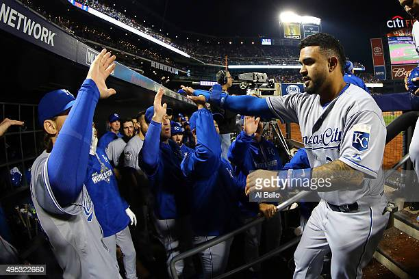 Christian Colon of the Kansas City Royals celebrates in the dugout after scoring in the 12th inning against the New York Mets during Game Five of the...
