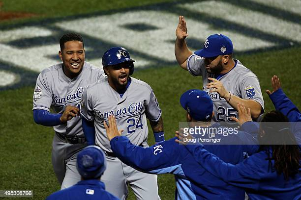 Christian Colon of the Kansas City Royals celebrates with his teammates after scoring in the 12th inning against the New York Mets during Game Five...