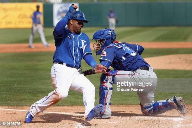 Christian Colon of the Kansas City Royals is tagged out by catcher Robinson Chirinos of the Texas Rangers during the second inning of the spring...