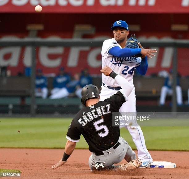 Christian Colon of the Kansas City Royals throws to first past Yolmer Sanchez of the Chicago White Sox for a double play in the first inning at...