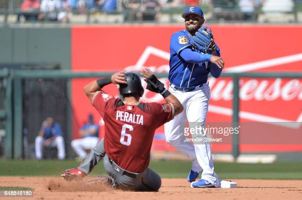 Christian Colon of the Kansas City Royals turns the double play over the sliding David Peralta of the Arizona Diamondbacks in the fourth inning of...