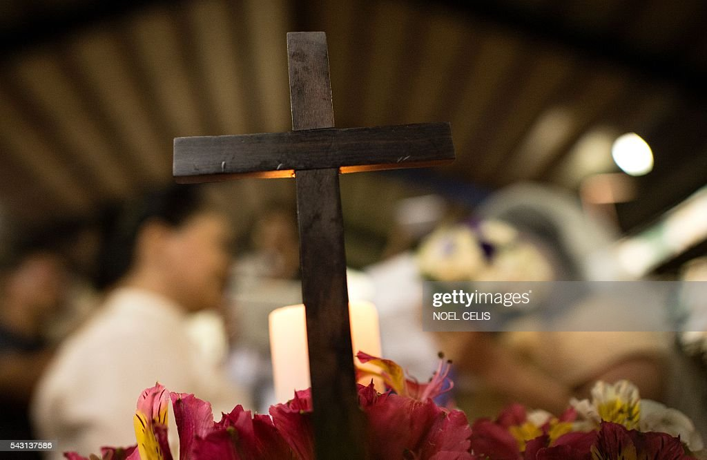 A Christian cross is pictured as couples from the lesbian, gay, bisexual and transgender (LGBT) community take part in a 'Rite of Holy Union' ceremony in Manila on June 26, 2016, that coincided with Gay Pride celebrations the day before. The Philippines has a vibrant gay scene despite a macho culture and opposition from the Roman Catholic Church, but there are no anti-discrimination laws in the country and same-sex relationships are not officially recognised. / AFP / NOEL