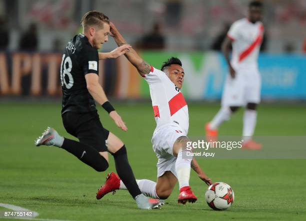 Christian Cueva of Peru slides for the ball while Kip Colvey of New Zealand tries to kick during a second leg match between Peru and New Zealand as...
