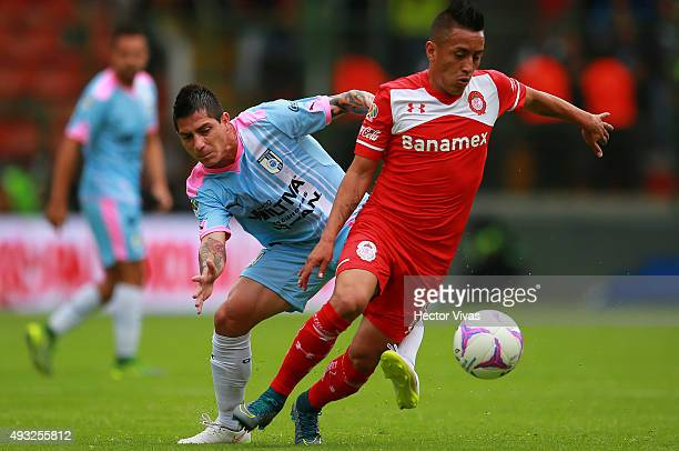 Christian Cueva of Toluca struggles for the ball with Danilo Veron of Queretaro during the 13th round match between Toluca and Queretaro as part of...