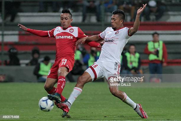Christian Cueva of Toluca vies for the ball with Michael Orozco of Tijuana during their Mexican Apertura football tournament match at the Nemesio...
