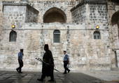 A Christian custodian of the Church of the Holy Sepulchre wears a Fez and carries a sword and a heavy metaltipped walking stick as he walks past two...