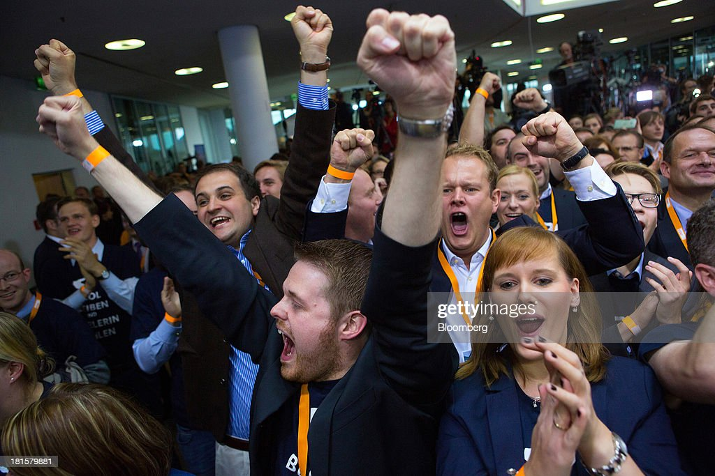 Christian Democratic Union (CDU) supporters react at the CDU headquarters as the German federal election result is announced in Berlin, Germany, on Sunday, Sept. 22, 2013. Merkel, Germany's chancellor and party leader of the Christian Democratic Union (CDU), won an overwhelming endorsement from German voters, putting the country's first female chancellor on course for the biggest election tally since Helmut Kohl's post-reunification victory of 1990. Photographer: Krisztian Bocsi/Bloomberg via Getty Images