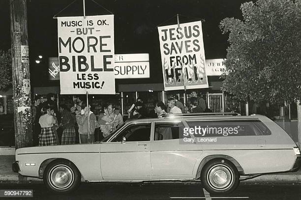Christian demonstrators protest outside a punk rock show at the Starwood They carry signs reading 'Jesus Saves from Hell' and one that implores...
