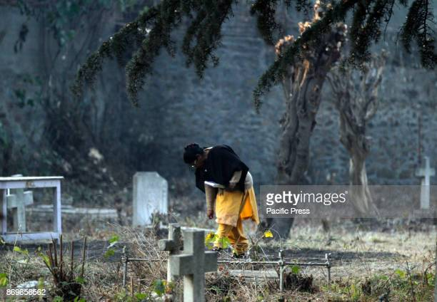 Christian devotee walks in a local cemetery in Srinagar the summer capital of Indian controlled Kashmir All Souls' Day commemorates the remembrance...