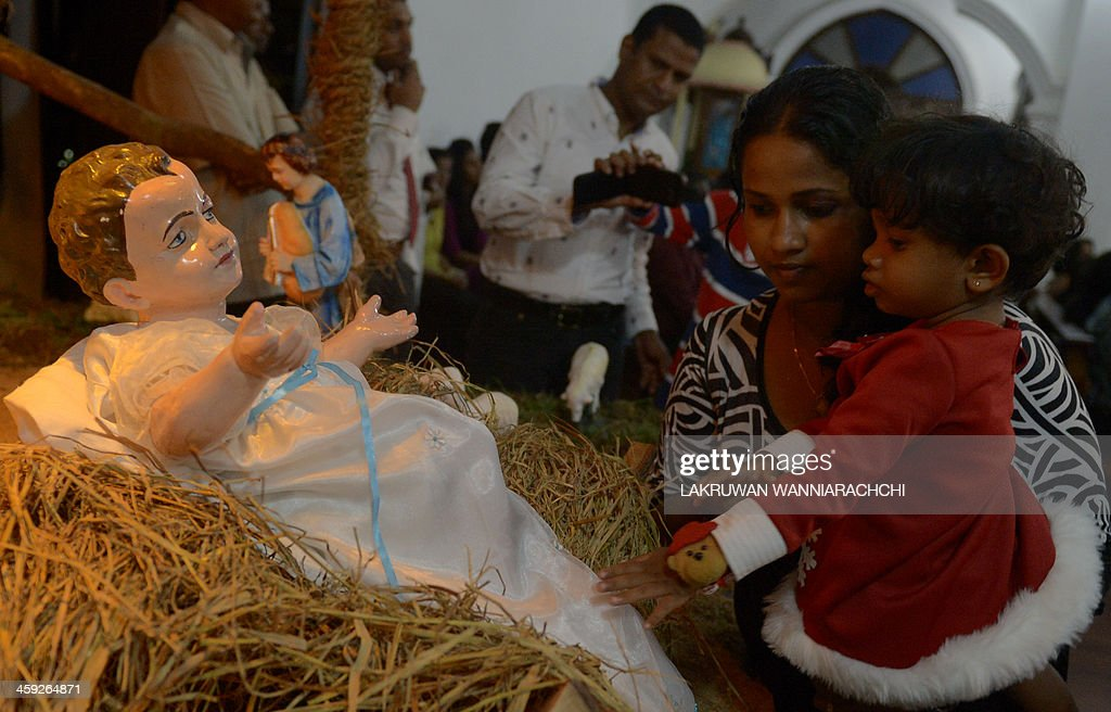 Christian devotees gather around the nativity scene depicting the birth of Jesus during a Christmas mass in Colombo early on December 25, 2013. Christians account for some 6 per cent of Sri Lanka's 21 million population. AFP PHOTO / LAKRUWAN WANNIARACHCHI