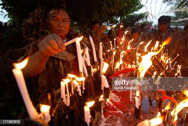 Christian devotees light candles in celebrating the Taong Putik Fesitival commemorating their patron Saint John the Baptist in Alliaga township on...