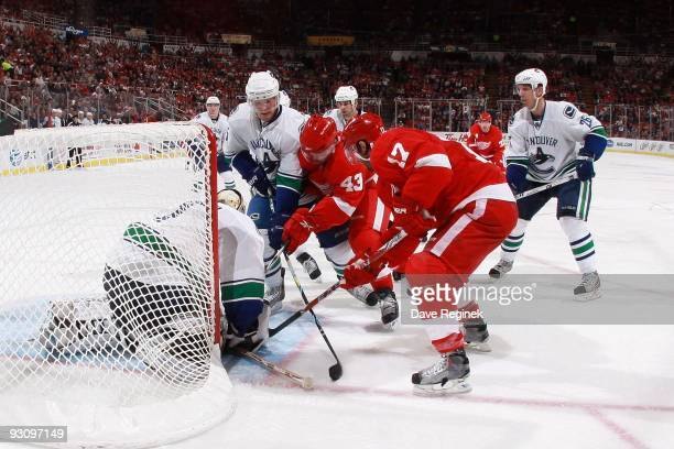 Christian Ehrhoff and goaltender Roberto Luongo Vancouver Canucks defend the net against Darren Helm and Patrick Eaves of the Detroit Red Wings look...