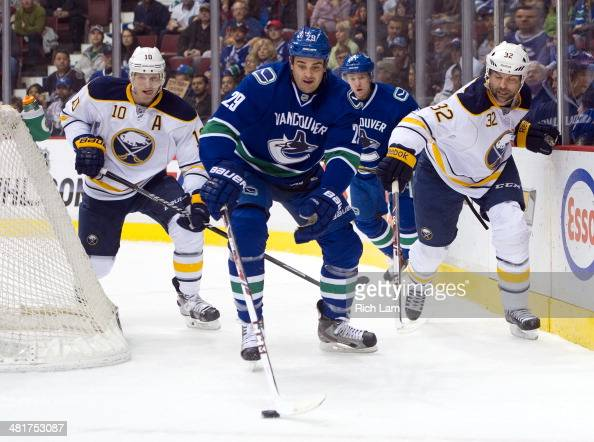 Christian Ehrhoff of the Buffalo Sabres and John Scott try to check Tom Sestito of the Vancouver Canucks off the puck during NHL action on March 23...