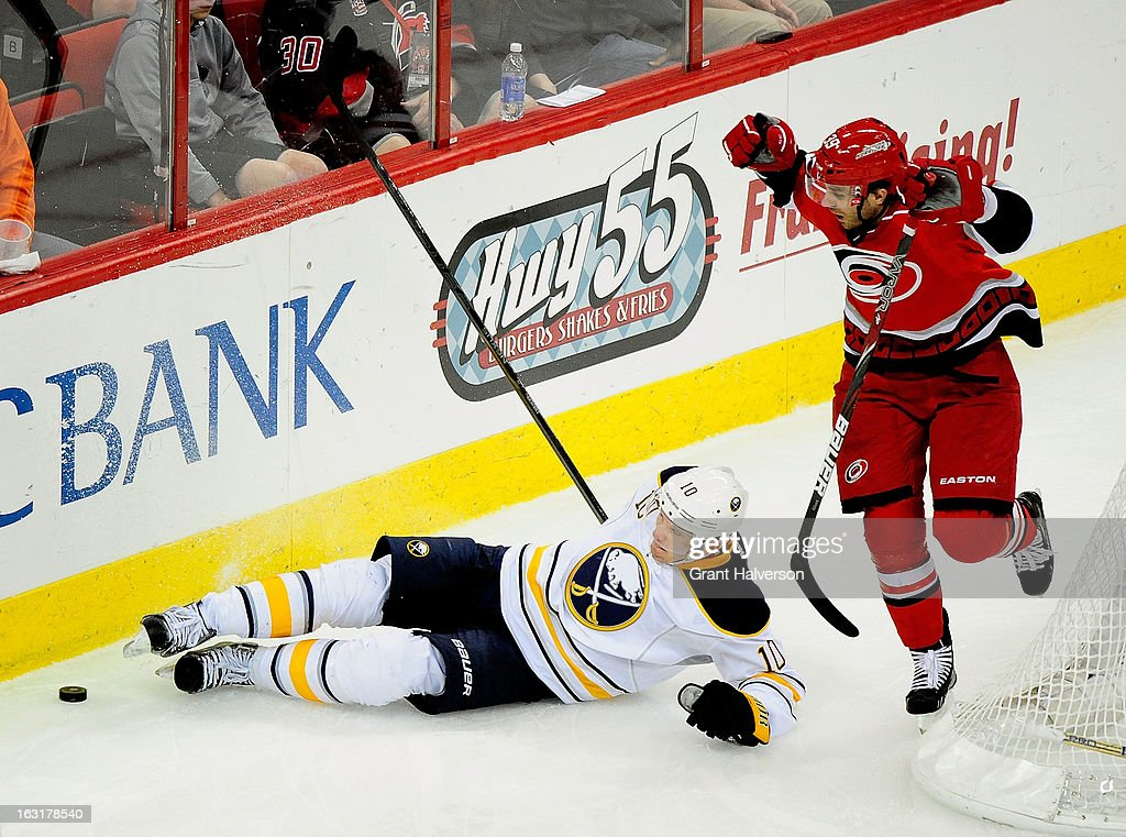 Christian Ehrhoff #10 of the Buffalo Sabres battles for a puck behind the net with Patrick Dwyer #39 of the Carolina Hurricanes during play at PNC Arena on March 5, 2013 in Raleigh, North Carolina. The Hurricanes won 4-3.