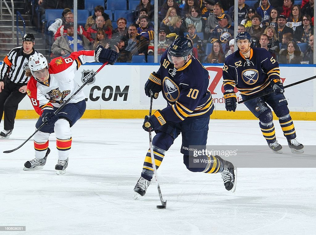 Christian Ehrhoff #10 of the Buffalo Sabres passes the puck in front of teammate Alexander Sulzer #52 and Peter Mueller #88 of the Florida Panthers on February 3, 2013 at the First Niagara Center in Buffalo, New York.