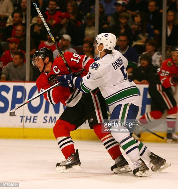 Christian Ehrhoff of the Vancouver Canucks pushes Jonathan Toews of the Chicago Blackhawks at the United Center on October 14 2009 in Chicago...