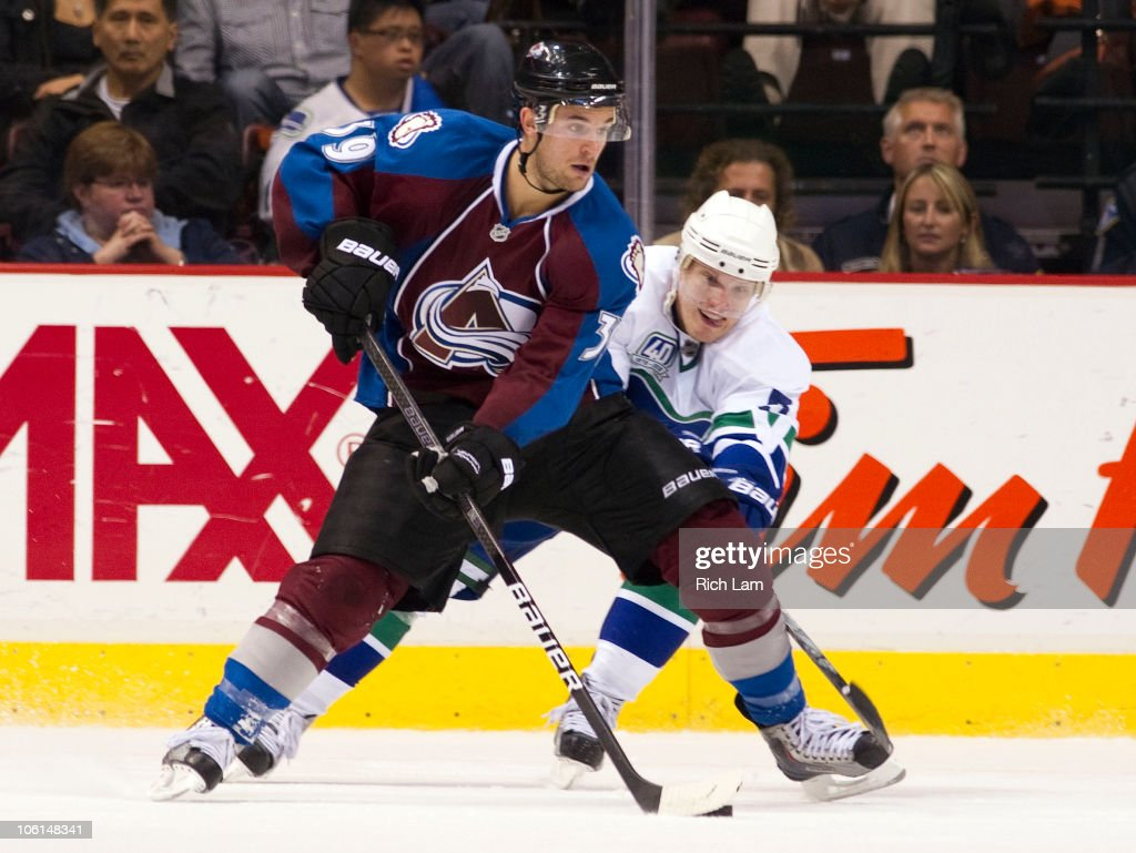 <a gi-track='captionPersonalityLinkClicked' href=/galleries/search?phrase=Christian+Ehrhoff&family=editorial&specificpeople=214788 ng-click='$event.stopPropagation()'>Christian Ehrhoff</a> #5 of the Vancouver Canucks tries to poke the puck away from TJ Galiardi #39 of the Colorado Avalanche during the third period in NHL action on October 26, 2010 at Rogers Arena in Vancouver, British Columbia, Canada.