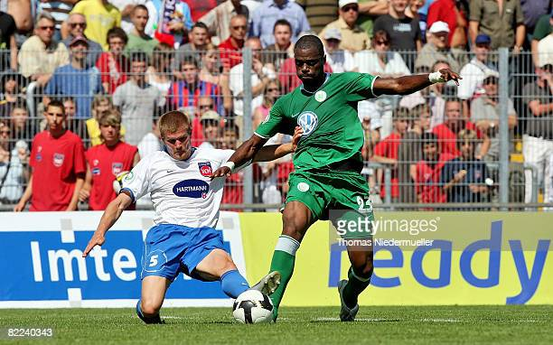 Christian Endler of Heidenheim fights for the ball with Batista Libanio EdinaldoGrafite of Wolfsburg during the DFB Cup first leg match between 1 FC...