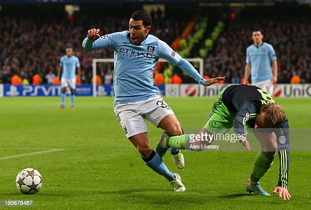 Christian Eriksen of Ajax tangles with Carlos Tevez of Manchester City during the UEFA Champions League Group D match between Manchester City FC and...
