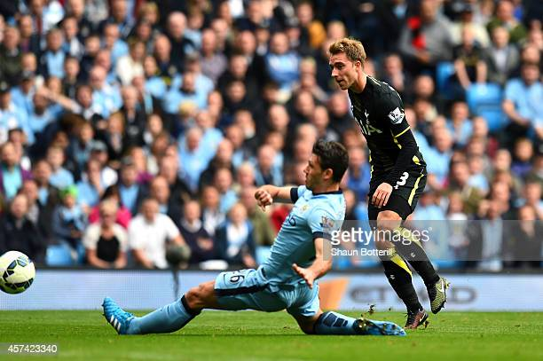 Christian Eriksen of Spurs shoots past Martin Demichelis of Manchester City to score a goal to level the scores at 11 during the Barclays Premier...