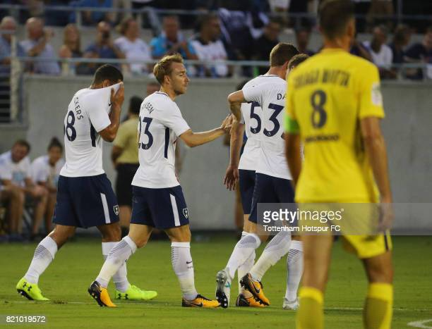 Christian Eriksen of Tottenham Hotspurs celebrates with his teammates after scoring a firsthalf goal against Paris SaintGermain during a...