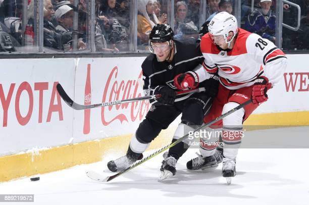 Christian Folin of the Los Angeles Kings battles for the puck against Elias Lindholm of the Carolina Hurricanes at STAPLES Center on December 9 2017...
