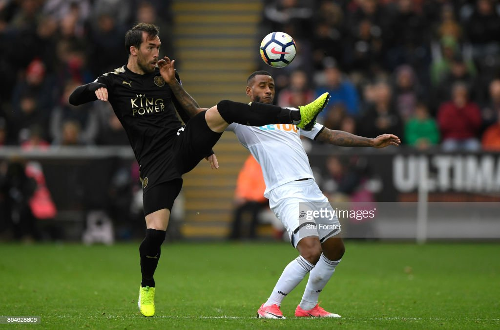 Christian Fuchs of Leicester City and Luciano Narsingh of Swansea City clash during the Premier League match between Swansea City and Leicester City at Liberty Stadium on October 21, 2017 in Swansea, Wales.