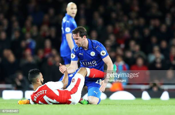 Christian Fuchs of Leicester City helps Theo Walcott of Arsenal to his feet during the Premier League match between Arsenal and Leicester City at...
