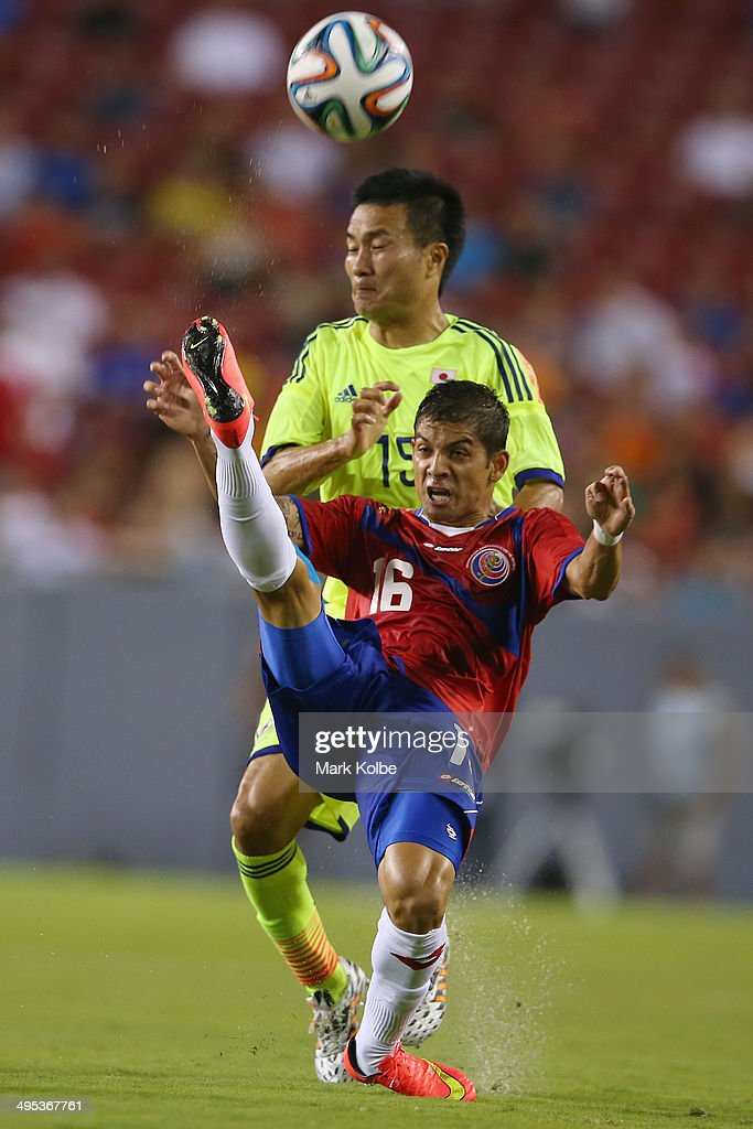 Christian Gambo of Costa Rica clears the ball under pressure from <a gi-track='captionPersonalityLinkClicked' href=/galleries/search?phrase=Yasuyuki+Konno&family=editorial&specificpeople=2358762 ng-click='$event.stopPropagation()'>Yasuyuki Konno</a> of Japan during the International Friendly Match between Japan and Costa Rica at Raymond James Stadium on June 2, 2014 in Tampa, Florida.