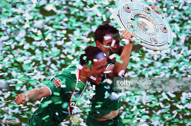 Christian Gentner and Sascha Riether of Wolfsburg celebrate the German championship with the trophy after their Bundesliga match against SV Werder...
