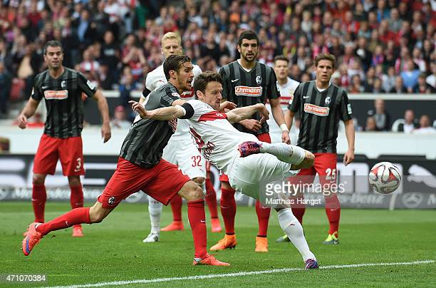 Christian Gentner of Stuttgart is challenged by Julian Schuster of Freiburg during the Bundesliga match between VfB Stuttgart and SC Freiburg at...